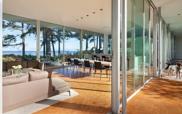 View into the open living dining kitchen space and the transparency of the sliding glass doors