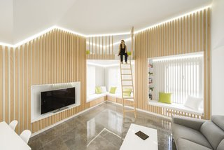 A mobile ladder leads to the bonus room, which serves as a guest room or reading nook.