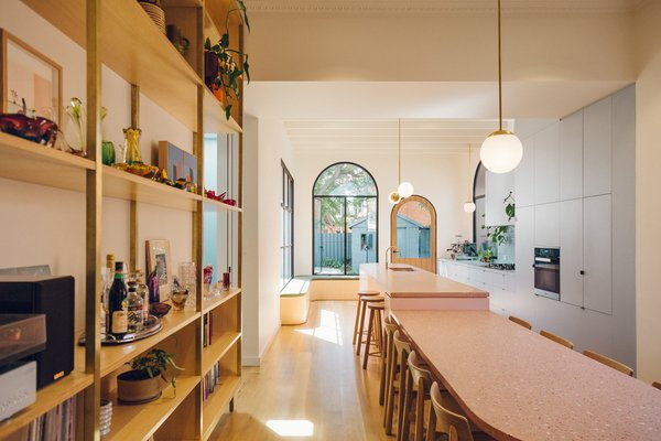 The long pink terrazzo island effortlessly joins the original dining area with the renovated kitchen.