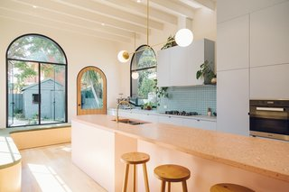 An elongated, pink terrazzo kitchen island accommodates larger gatherings; it extends all the way into the dining area. Powder-blue cabinets provide a cool contrast.
