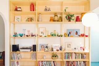 The bookshelves provide ample storage and display space for the homeowners' glassware and pottery collection.