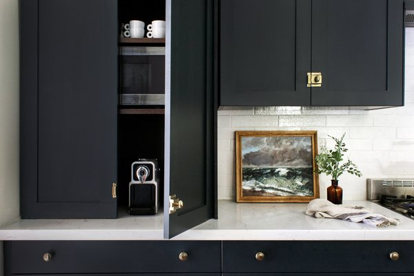 One of Catherine Williamson's favorite Semihandmade cabinets includes this appliance cabinet, which keeps things out of sight. The piece of art to the right is a vintage portrait from her grandparents.