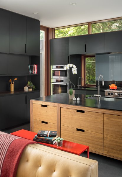The black Richlite and walnut kitchen is one of Mongillo's favorite elements of the home. He says that kitchens often feel out of place—but this one is an architectural feature, with the island acting as another piece of furniture.