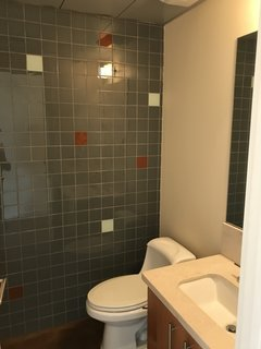 The original bathroom had dingy lighting and mismatched materials.
