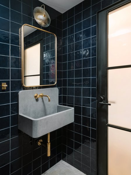 """While the rest of the loft is bright and airy, the team wanted to create a moodier look for the powder room. """"We used darker handmade tile (Mano from the Cev Series in Cobalt from DDS) and found these concrete sinks from the UK (Elm Sink from Kast Concrete) that can be made any size you want,"""" Francis says. """"We used brass fixtures to finish it off."""""""