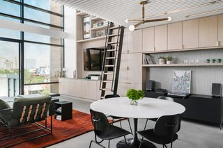 "Bjorndahl hoped for a great room that would feel ""curated and orchestrated, much like a tailored suit."" To achieve this goal, the team used cabinetry from Elmwood Fine Cabinetry in New Haven for the kitchen, the living room, the office, and the master bath. The home's first floor measures approximately 1,000 square feet. The dining area features a 60-inch round table from Design Within Reach and Eames molded plywood dining chairs from Workplace Resource."