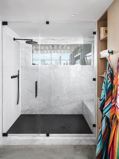 "The design team transformed the master bathroom into a luxurious en suite with a white-and-black marble rain shower and multicolored his-and-hers robes from Austin's Hotel San Jose. The team also punched a window through the back wall of the office to allow natural light to permeate the room. ""The window is switch glass and can be turned on and off for privacy while in the shower, but still provides a view of downtown."""