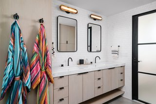 Brass lights from Apparatus Studio provide extra lighting in the bathroom. The space is complete with Alexander Marchant sinks and faucet, hardware from Schoolhouse Electric and the same cabinetry seen throughout the rest of the loft.