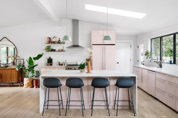 The kitchen is painted in Setting Plaster by Farrow and Ball. The Fibre bar stools and Ambit pendants are from Muuto.