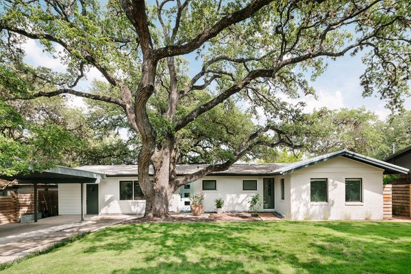 The real stars of this 1950s ranch home are the two giant live oaks that live in the front and back yards. To let the landscaping stand out, the Lemmos painted the exterior Woodland White by Benjamin Moore and matched the front door to the beautiful blue master bathroom vanity.
