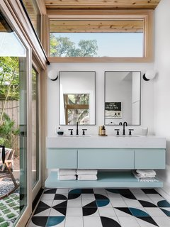 The master bathroom uses black-and-white finishes to enhance the home's pastel palette.