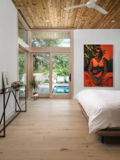 The homeowners chose this large, richly colored painting by Austin-based artist Patrick Puckett to be the focal point of the master bedroom.
