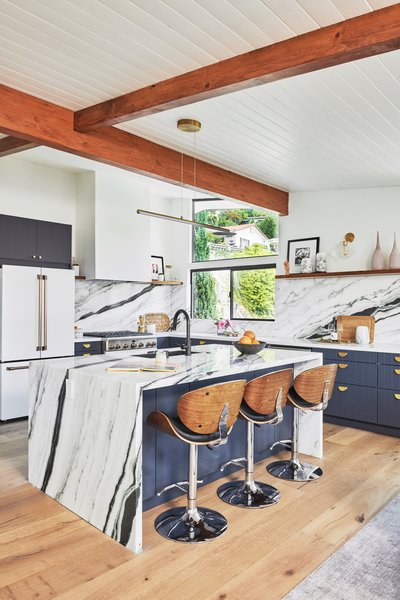 "The Raskinds designed an open-concept kitchen with midcentury charm using Dunn Edwards paint in Deepest Sea and West Elm light fixtures. They replaced the original cabinetry with Semihandmade cabinetry, and built an island with a white-and-black marble slab from Stoneville. ""We found this great panda-colored slab and knew we wanted to do a waterfall island to elevate the look of the IKEA doors,"" she says."
