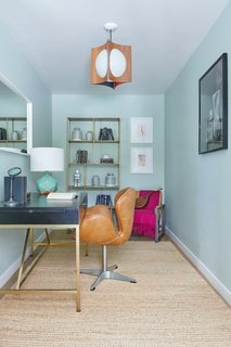 The office is the ultimate blend of the Raskinds design styles: Hollywood Regency and California Eclectic. The walls are a sage green color, Granite from Dunn Edwards, and the room features a 1960s pendant that originally hung in the home's master bedroom.