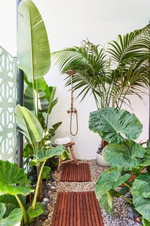 "The Raskinds upgraded the side yard by installing an outdoor shower, something that Rebecca Raskind feels is ""having a moment right now."" They also sourced tropical plants inspired by Bali for a vacation vibe."