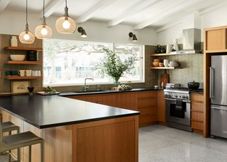 "The built-in hardware is one of Simon's favorite elements of the kitchen. ""We liked the idea of not having a lot of jewelry in this room,"" she says. The pendant lights are from Shades of Light, the bar stools from Interlude Home, the wall sconces from Cedar and Moss, and the accessories are from Everything But the House, an online auction house."