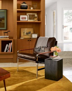 A cozy leather chair anchors the living room and adds traditional flair. The bookshelves are decorated with personal items, a Samsung television that looks like a piece of art, and a miniature horse statue Simon bought in Round Top.