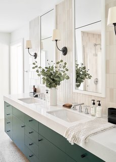 The master bathroom is the only spot in the home that features actual hardware. Simon went with a rich blue-green tone for the double vanity and Colton wall sconces from Y Lighting.