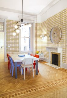 The dining room is for the kids with funky blue and red chairs, gold Ellie Kishimoto wallpaper that is reminiscent of the ornate wallpaper that may existed in this home in the 19th century, and a large table. The fireplace, which is original, was recovered in marble.
