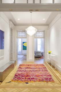 """The foyer was decorated simply with a stainless-steel bench, vintage rug, and vintage light fixture. """"The hand-blown glass fixture has this beautiful, iridescent quality at different angles,"""" Flam says.  """"It's enough to offset the room without cluttering it."""""""