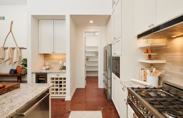 The open kitchen is equipped with plenty of flexible cabinet space, open shelving, and built-in wine storage.