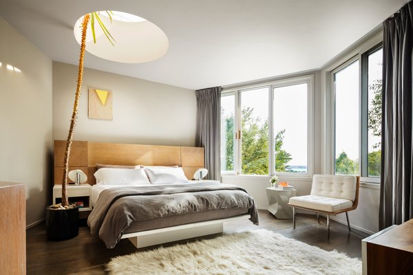The master bedroom provides peaceful views of the Long Island Sound and includes a king bed, designed by Rottet herself, outfitted with Restoration Hardware linen and a funky skylight—which accommodates a tropical tree.