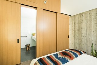The master suite features a monochromatic bathroom, which rests inside the white oak form, and a king bed with West Elm textiles.