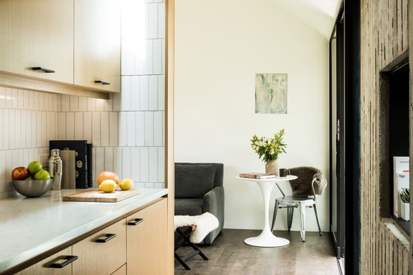 """The kitchenette features ridge-sawed white oak cabinetry and white 2"""" x 8"""" subway tiles. """"The tiles were a very reasonable price, which allowed us to do more with the space,"""" Finnell says."""