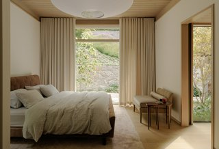 The master bedroom is now a sophisticated retreat with a meaningful connection to the backyard. A Ted Boerner bed purchased at San Francisco's HEWN rests atop a Rug Company rug.