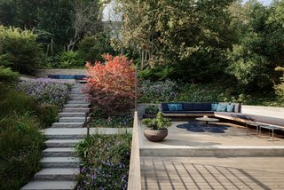 Paola Lenti furniture in rich navy and burgundy tones outfit the reimagined backyard, which also features chiseled retaining walls by a local stonemason. Japanese maple trees add to the zen-like atmosphere.
