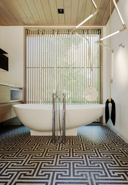 The funky master bath features stained white oak cabinetry by Eby Construction, Fantini fixtures, and a deep soaking tub. Mosaic tile, laid in a graphic pattern, echoes the angles of the abstract pendant light.