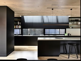 Since the renovation, the full-length window at the back of the kitchen is populated by dense greenery, offering even more privacy to the homeowners.