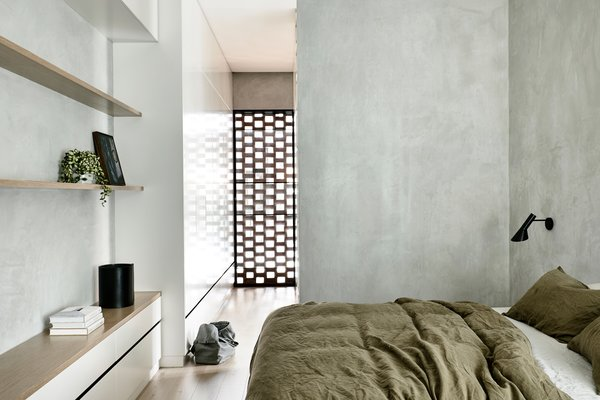 The master bedroom has become the ultimate haven with a clean concrete base, warm wooden flooring, matching built-in shelves, and access to the garden.
