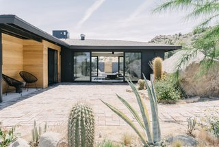 "The couple added a coat of black paint and cedar siding to give the home a cleaner, more modern look. ""The house already had wide and low eaves, providing protection from the sun, and we added new spray-foam insulation, so the black exterior actually does not pose too much of an issue with the desert heat,"" she says. A new Cor-Ten steel fence blocks the view of the neighbor's roof, but doesn't interfere with the landscape."