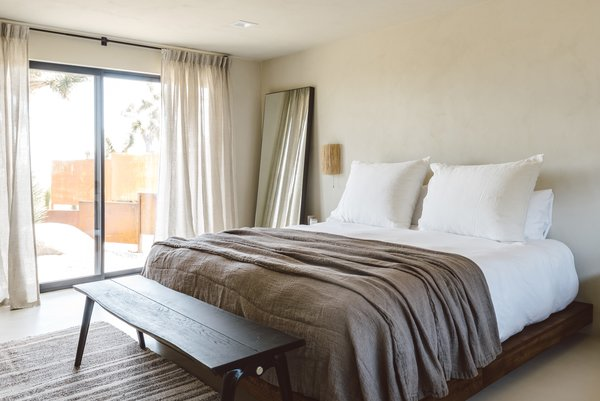 The master bedroom features a custom-made platform bed and curtains, a sconce with a rattan shade from Tine K Home, a vintage Turkish kilim rug, and Sika Design side tables.