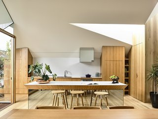 "The kitchen, built with imported Tasmanian oak and plywood, features one of the most beloved details from Pam's Cross-Stitch House—a kitchen island with a mirrored base—but the floating bench here is shaped differently to represent Arthur. ""[The mirror] lightens the space in many ways, so you don't feel like the island is taking over,"" says Dunin. Graphic backsplash tiles fom Academy Tile run into laminate countertops with a plywood edge. The refrigerator is Fisher & Paykel, and the combo oven and cooktop is V-ZUG."
