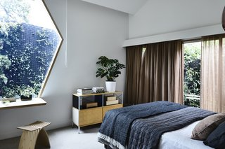 The bedroom feels secluded and looks out to a garden. The credenza is from Herman Miller and the circular bedspread is from HAY.