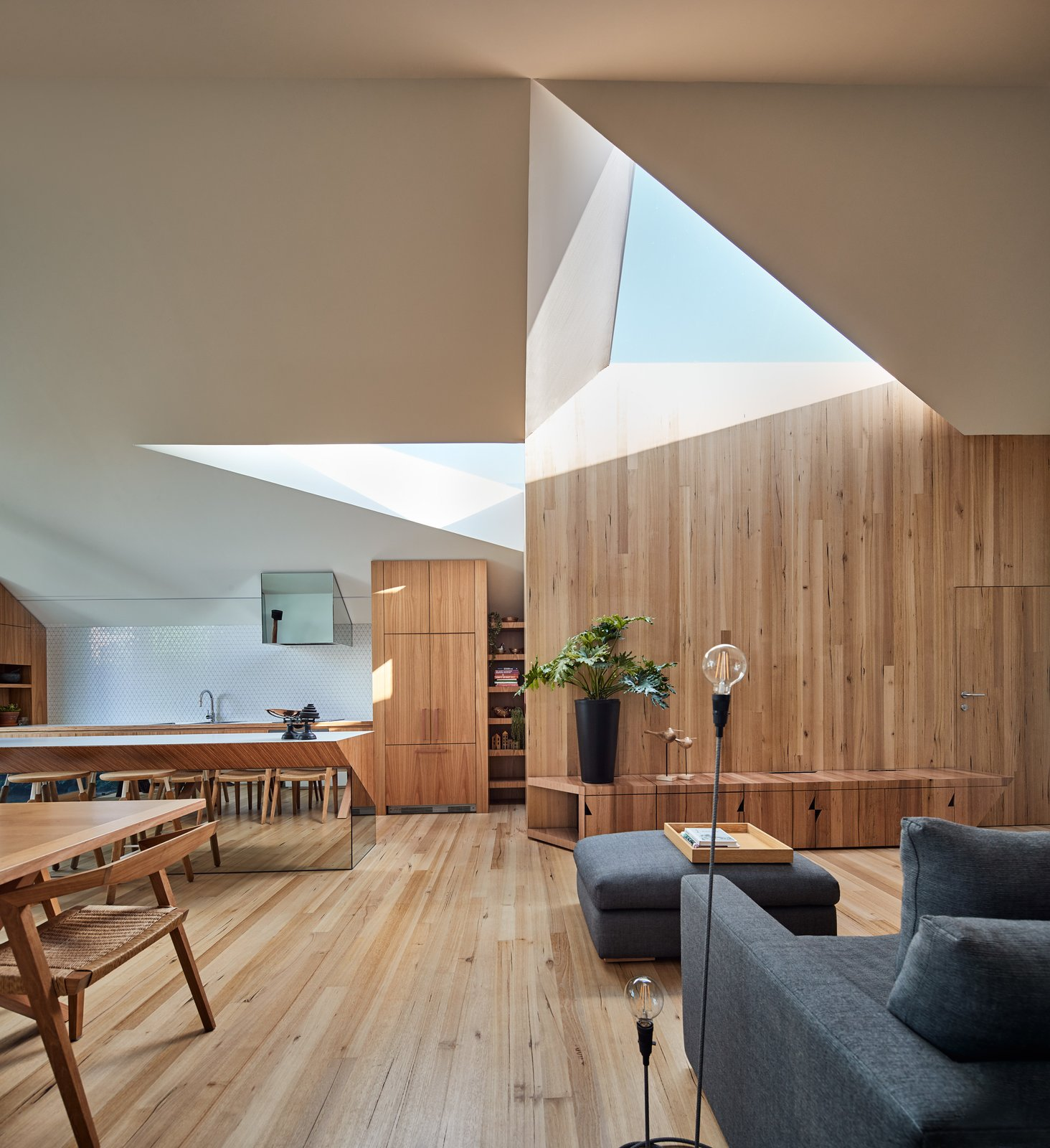 His and Hers House by FMD Architects living room with triangular skylights