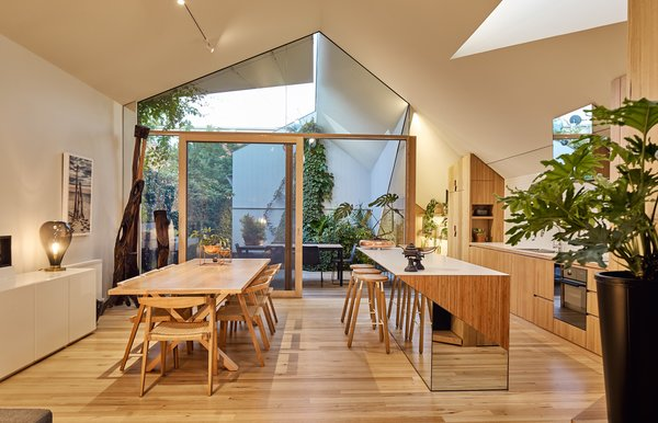 "The pitched ceiling soars to nearly 15 feet high, ""giving a grand sense of scale and volume,"" says Dunin. The effect is underscored by triangular skylights that brighten up the dining space, which holds a table by Jardan and the chairs by FeelGood Designs."