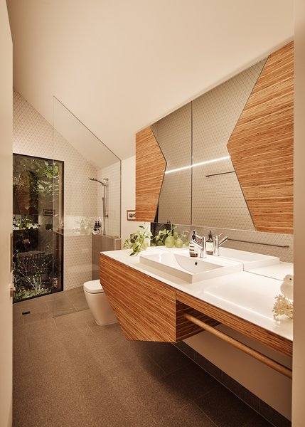 The bathroom has shapes meant to represent Pam and Arthur, and brings in the same tile used in the kitchen. The countertop is Corian, and the cabinet fronts are plywood.