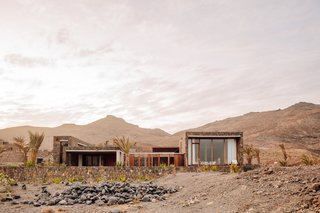 The one-story homes blend seamlessly into the background due to a palette of basalt, cement, and imported African wood.