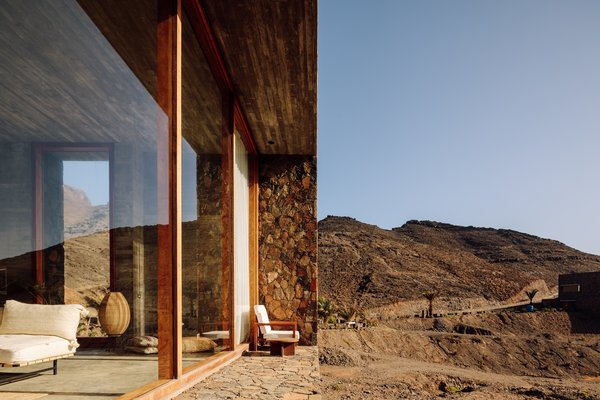 The 15-foot windows provide breathtaking views of the surrounding hills and blue ocean waters.