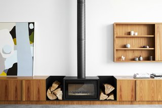 """Buckets sit around the fireplace to hold the firewood and provide a nice contrast between the cabinetry,"" Harding says. The bold black Stovax fireplace is the primary statement in the living room, however it also displays the homeowners' curated items and a piece of art by Clare Brody from Studio Gallery in Melbourne."