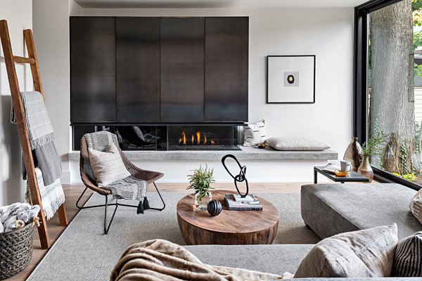 The living room offers a touch of Nordic simplicity with a combined steel TV unit and fireplace from Space Furniture, rattan chair from IKEA, C-shape gunmetal table from Casalife, and art from Cocoon Furnishings.