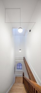 "To bring natural light into the center of the home, LeBlanc inserted a thin skylight above the stairs. The chandelier is from Michael Anastassiaees. ""We wanted to find something contemporary that had nice lines,"" LeBlanc says. ""It seemed perfect because it acts like a 3-D mobile and has the geometric qualities Kevin likes in art."""
