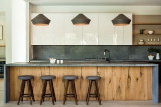 The kitchen features a honed Ceasarstone rugged concrete island, concrete backsplash, antique white oak cabinetry, Thermador appliances and tobacco-stained oak base cabinetry.