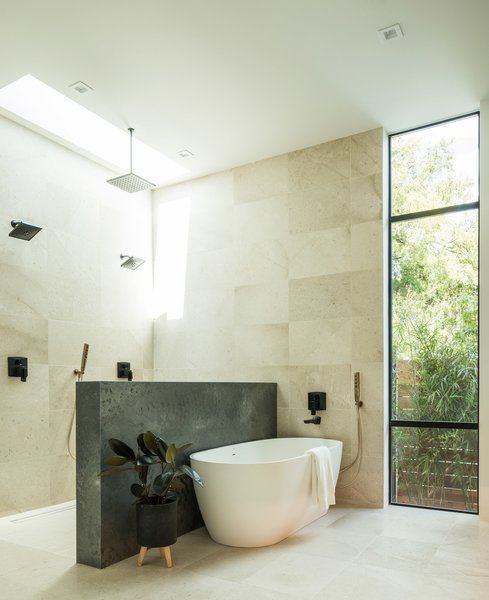 """We really wanted to enhance natural lighting so the shower has a skylight in it to luminate the space during the day,"" Frank Lin says. The spa-like space includes concrete countertops, antique white oak cabinets, and limestone tile floors."