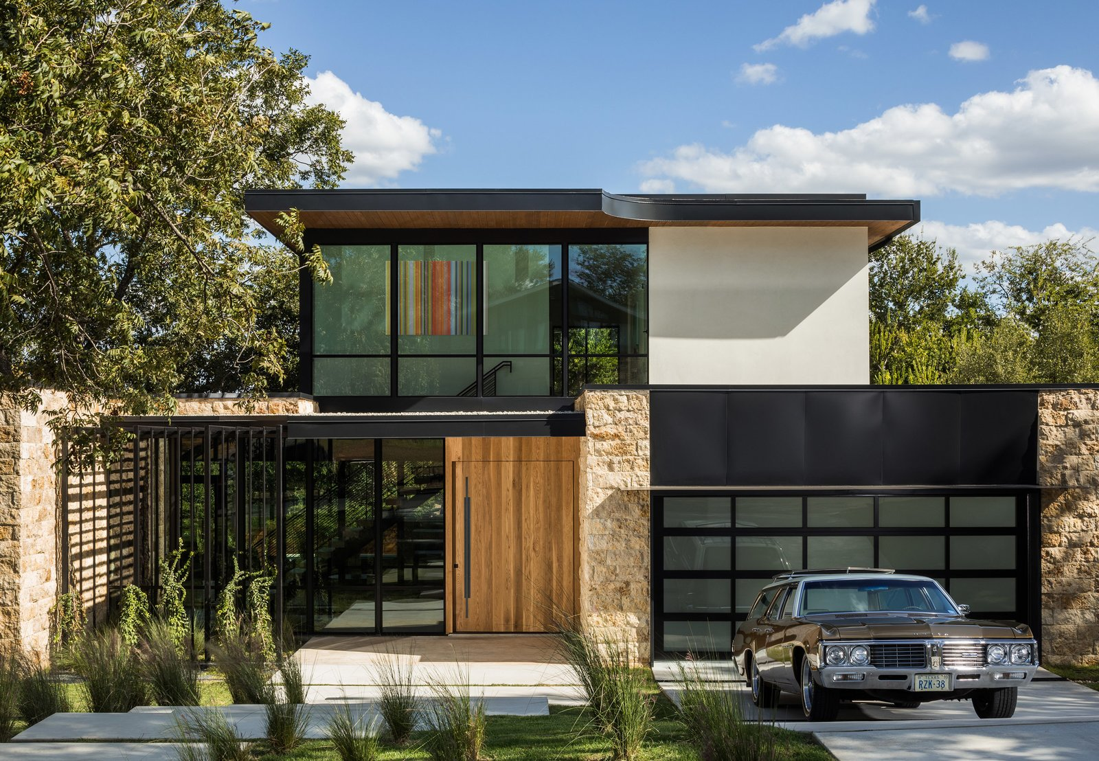 the exterior features thermally broken windows a pivot white oak front door and walden 12 inch led wall lights in textured black finish from kichler lighting
