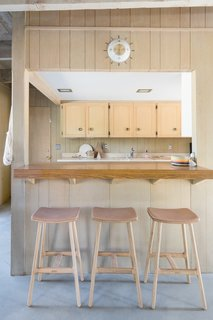In the kitchen, Lewis was in awe of the beautifully restored cabinetry and wooden details, and wanted to leave things as is. She then added barstools from Article.