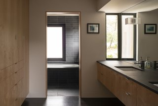 The clean cabinetry and moody tiling yield a relaxing upstairs master bath.